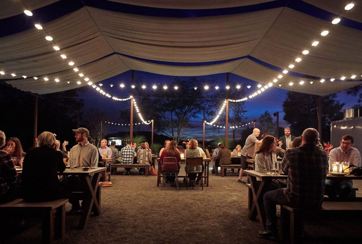People Dining under a canvas tent