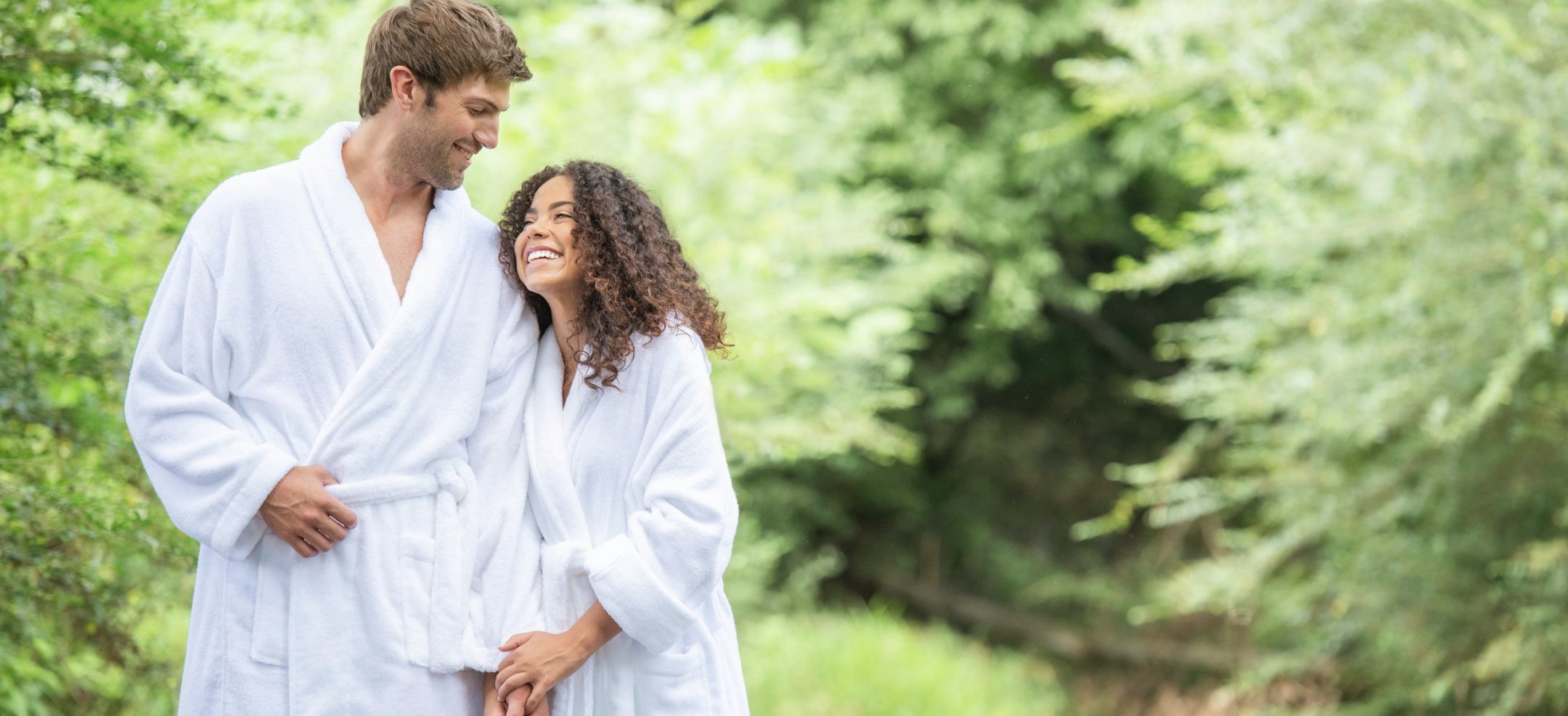 A couple in bath robes holding hands